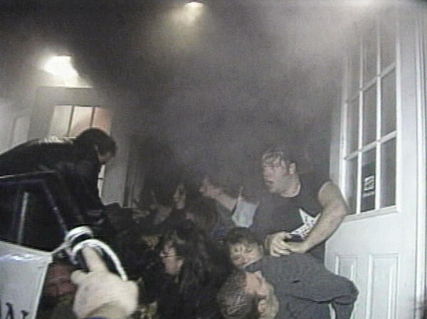 In this image from video shot by TV station WPRI, people try to escape a fire at The Station nightclub using the front exit of the building. Fire broke out during a performance and pyrotechnic display by the band Great White.  In an interview with CNN, the band's lead singer Jack Russell said that the flames from the pyrotechnic display spread to foam decorations around the stage.