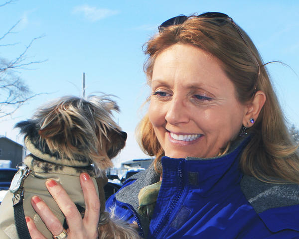 Gaeyle Gerrie-Boss of Boyne City comforts her blanketed Yorkshire terrier, Misha, Saturday as they visit the children¿s game time at Old City Park during Winterfest in Boyne City.
