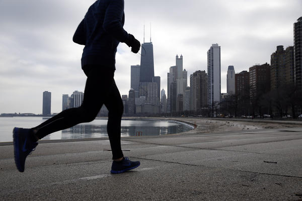 A jogger runs near North Avenue Beach in Chicago. The unusual warmth is forecast to continue another day.