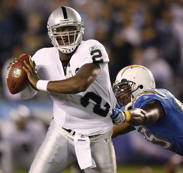 Oakland quarterback JaMarcus Russell tries to escape San Diego's Shaun Philips