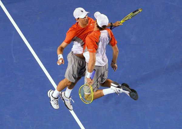 Mike Bryan (L) and his brother Bob of the US celebrate after their victory over the Netherland's Robin Haase and Igor Sibling during the men's doubles final on day 13 of the Australian Open tennis tournament in Melbourne early on January 27, 2013.