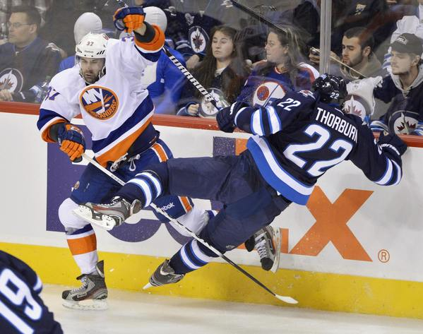 New York Islanders' Brian Strait (L) checks Winnipeg Jets' Chris Thorburn during the third period of their NHL hockey game in Winnipeg January 27, 2013.