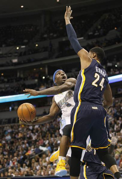 Denver Nuggets guard Ty Lawson (L) drives the lane against Indiana Pacers forward/guard Paul George (24) in their NBA basketball game in Denver January 28, 2013.