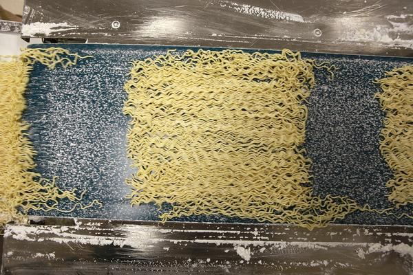 """Freshly cut ramen noodles move along a conveyor belt. One noodle type made for a restaurant in Texas is called TS24W. The TS stands for tokusen, which means """"specially selected."""" The 24 indicates that 24 noodles are cut from a width of 3 centimeters of dough. The W means the noodles are wavy."""