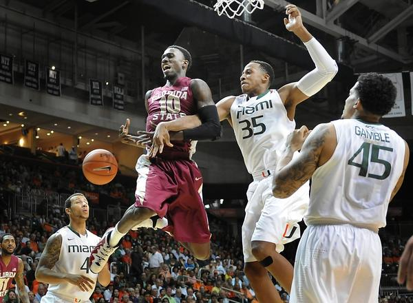 The Florida State Seminoles visit the University of Miami Hurricanes at the BankUnited Center. Miami's Kenny Kadji knocks the ball away from Florida State's Okaro White just as White was going for the layup.