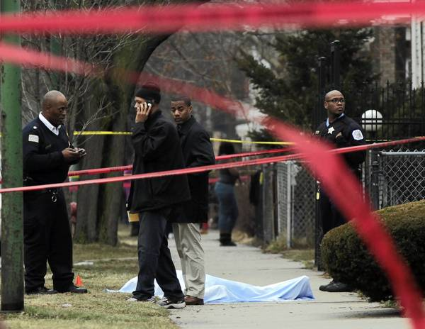 Chicago Police investigate near the body of a shooting victim on S. Champlain Avenue near 75th Street in Chicago.
