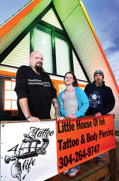 "From left, staff members Bob ""Butane"" Ewers and Tara ""Ms. Body Bling"" Patrick, and co-owner Jason Stevens stand outside Little House of Ink at 32 Bowling Lane in Martinsburg, W.Va."