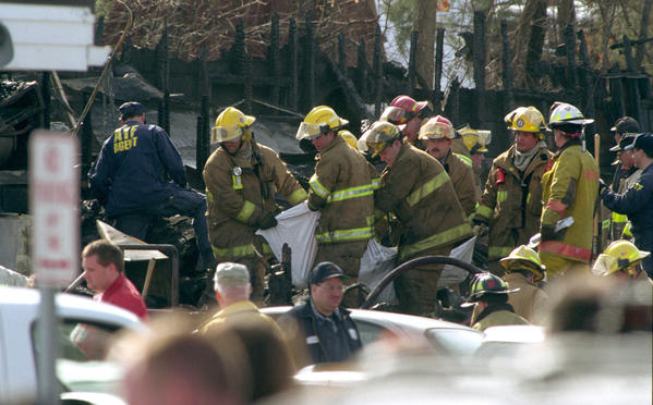 (GRAPHIC IMAGE) Firefighters carry a body bag through the wreckage of The Station nightclub as they continue to recover the bodies of victims.