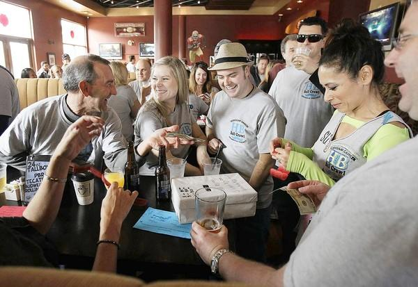 Jane Boltz, right, sells raffle tickets to Brian Shea, left, Jackie Brzybelinski, and Liam Cahalane, in the hat, during the Huntington Beach Ball Crawl on Saturday. The money raised from T-shirt and raffle ticket sales during the pub crawl goes to testicular cancer awareness.