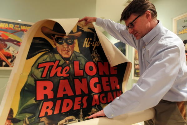"Movie poster collector Dwight Cleveland unrolls a poster for ""The Lone Ranger Rides Again,"" at his home in Chicago."