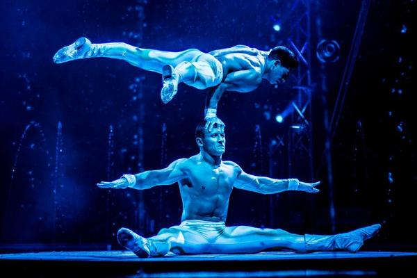 Surrounded by fountains, Cirque Italia performers demonstrate strength and balance.