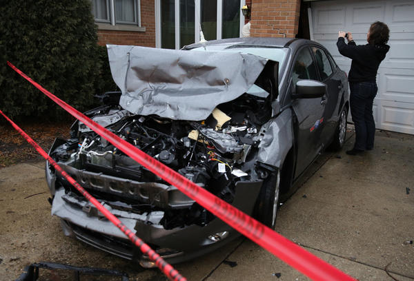 A damaged car rests against a house after it was spun around and hit by a school bus in the 900 block of Oakton Street in Niles. The bus struck several cars and only the driver was aboard.