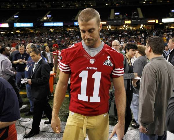 San Francisco 49ers quarterback Alex Smith walks on the field after he was not given a booth to answers question from journalists during Media Day.