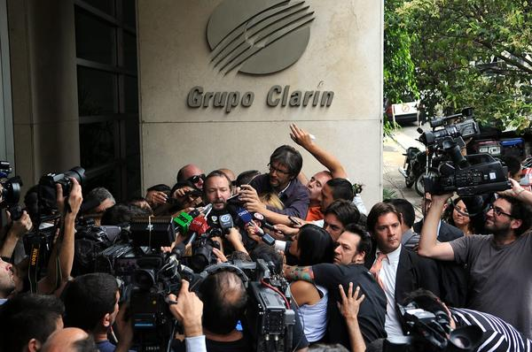In Argentina, the media giant Grupo Clarin has been threatened with the loss of its television licenses, reportedly because it has criticized government policies. Above: The head of the Federal Authority of Audiovisual Communication Services, Martin Sabbatella, center, speaks to members of the media after leaving the headquarters of Grupo Clarin in Buenos Aires on Dec. 17.