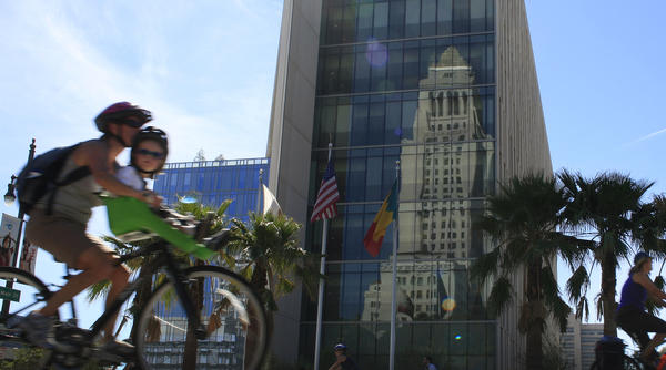 Los Angeles' city attorney is responsible for representing agencies, departments and politicians as well as the people of the city. Above: City Hall is reflected in the glass windows of the Los Angeles Police Department as cyclists ride along 1st Street.