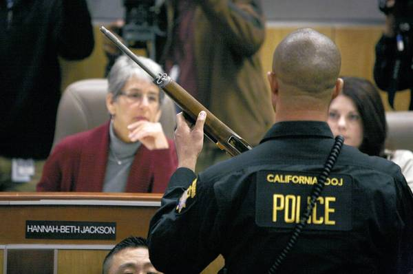 State Sen. Hannah-Beth Jackson (D-Santa Barbara) looks at a semi-automatic rifle during a joint legislative hearing on gun control. Testimony showed some of California's strict gun laws have been undermined by budget problems.