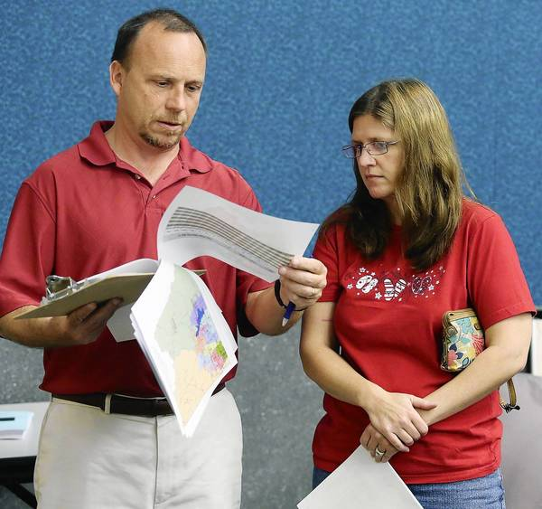 Timothy Berry, left, and Kelly Baker, both parents of students that will be affected, look over rezoning plans during a meeting at the Seminole County School Board office in Sanford on Tuesday, January 29, 2013.