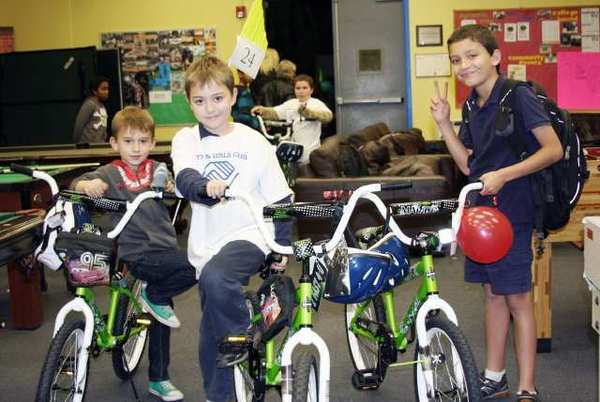 Boys & Girls Club members Dustin Ladd, Nico Tamburelli and Joshua Tamburelli with their new bicycles donated by DIRECTV employees.