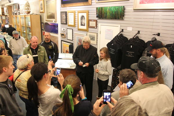 "Richard Harrison, one of TV's ""Pawn Stars,"" signs an autograph in his Las Vegas shop, which has become a tourist attraction."