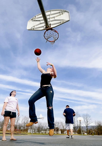 Lindsay Trumpower shoots a basket at Veterans Park in Smithsburg with Kirstin Mong, left, and D.J. Mong on Tuesday. The area experienced unseasonably warm temperatures.