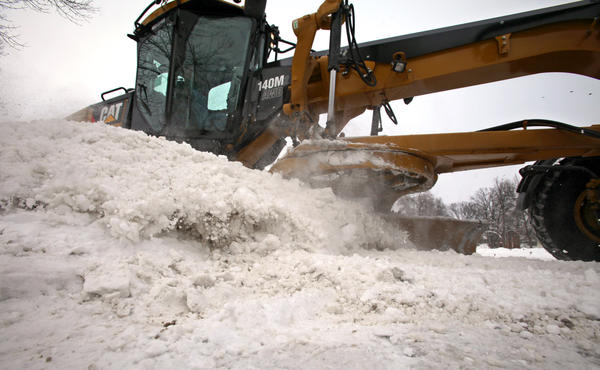 An Aberdeen Public Works Department snowplow makes a wave of snow as it clears through an intersection at 10th Avenue Southeast and South Kline Street Tuesday. City crews spent the day clearing the 8 inches of snow that fell on the area. American News Photo by John Davis