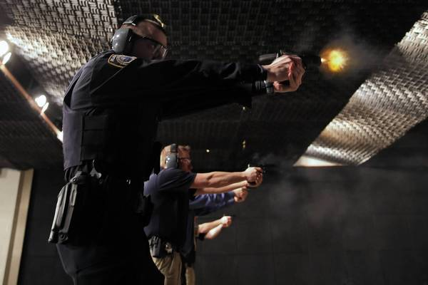 Plainfield police Officers Jason Rogers, left, and Brad Malcolm join fellow officers Tuesday in off-duty firearms qualification testing in Plainfield.