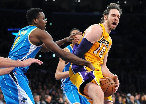 Lakers big man Pau Gasol is fouled by Hornets forward Al-Farouq Aminu while attempting a shot.