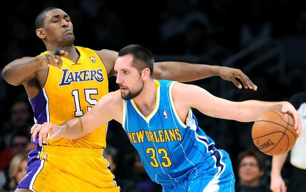 Hornets forward Ryan Anderson bumps into Lakers forward Metta World Peace while drive toward the basket.