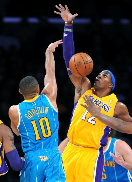 Lakers center Dwight Howard blocks a pass attempt by Hornets guard Eric Gordon.
