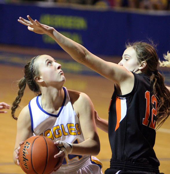 Aberdeen Central's Brianna Kusler, left, looks to shoot as Huron's Taya Butterfield, right, defends during the first half of Tuesday night's game at the Golden Eagles Arena.