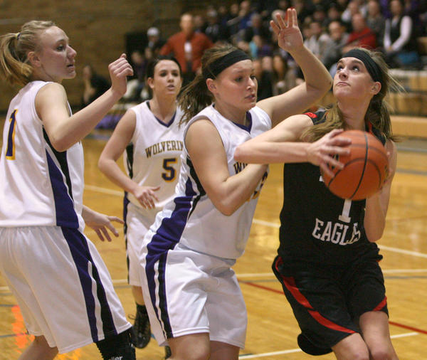 Logan O'Farrell, right, looks to the basket as she tries to drive past Herreid-Selby Area's Kelsey Quaschnick, center and Jana Thorstenson, left during Tuesday night's game at the Aberdeen Civic Arena. Looking on for the Wolverines is McKenzie Frank.