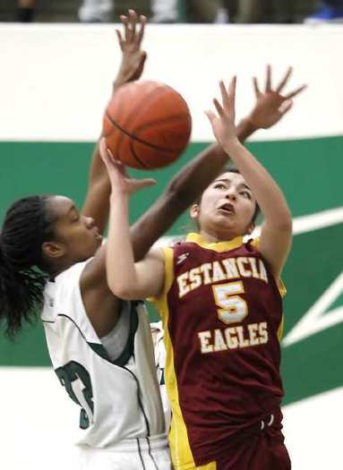 Estancia High's Celia Duran, right, drives to the basket as she is fouled by Costa Mesa's Aubriona Mathis in the Battle for the Bell game at Costa Mesa High.