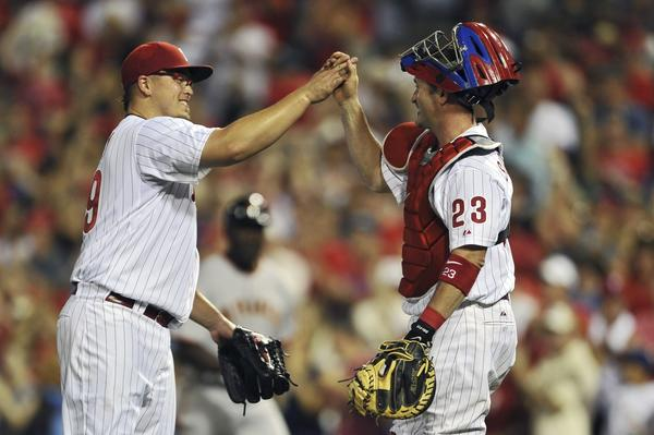 Starting pitcher Vance Worley #49 of the Philadelphia Phillies high-fives teammate Brian Schneider #23 after pitching a complete game and defeating the San Francisco Giants 7-2 at Citizens Bank Park on July 26, 2011 in Philadelphia, Pennsylvania.
