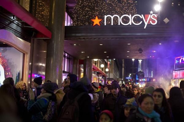Holiday shoppers crowd the sidewalk outside Macy's department store in New York City.