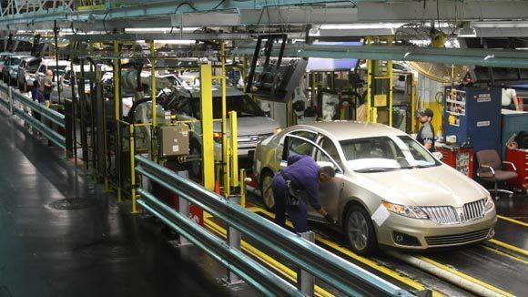 Workers check a car for gaps after the laser inspection at the Ford Motor Co. factory in Chicago.