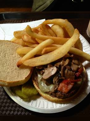 E.B. Burger, the house special, featuring Swiss cheese, bacon, mushrooms, and grilled onions, with French fries on the side.