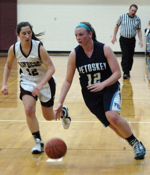 Petoskey senior forward/guard Kelsey Ance (right) dribbles near the baseline as Charlevoix's Sydney Carlson defends during Tuesday's non-league contest at the Charlevoix High School gym. The Northmen defeated the Rayders, 63-32, to collect a ninth-straight win.