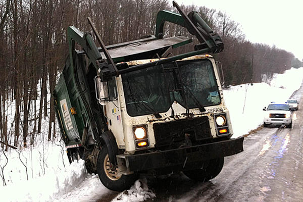 A fully-loaded Waste Management garbage truck, added by ice, slipped off of Clayton Road just north of Hiawatha Road, in Emmet County on Wednesday morning. There were no injuries reported.