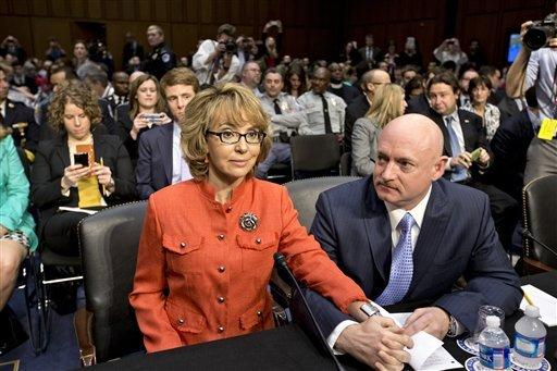 Former U.S. Rep. Gabrielle Giffords, D-Ariz., who was seriously injured in the mass shooting that killed six people in Tucson, Ariz. two years ago, sits with her husband, retired astronaut Mark Kelly, right, on Capitol Hill in Washington on Wednesday, prior to speaking before the Senate Judiciary Committee hearing on what lawmakers should do to curb gun violence in the wake of last month's shooting rampage at that killed 20 schoolchildren in Newtown, Conn.