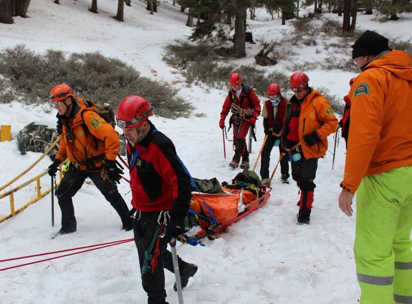 Montrose Search and Rescue and U.S. Forest Service deputies transport an injured hiker to safety on a snow litter.