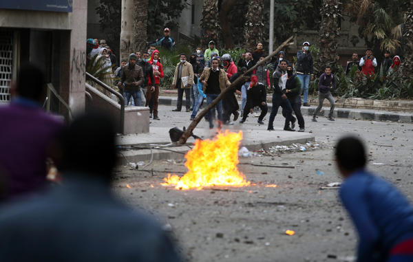 Pro- and anti-government protesters throw stones during clashes near Tahrir Square in Cairo.