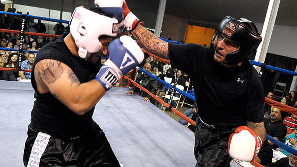 Darin Ayala of ATAP MMA (right) lands a punch on at Martin Islas of the US Army during a match at the When Forces Collide IV boxing match Saturday at the Imperial Valley Expo in Imperial.