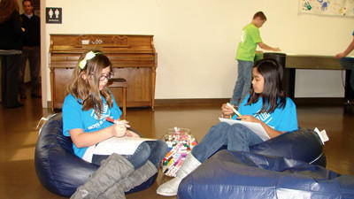 Olivia Hay and Angel Auxtero coloring in the new Boys & Girls Club.