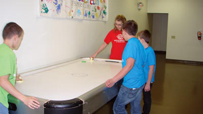 Tyler Rios, Ben Murdy, Charlie Samler and Sarah Humbert playing air hockey in the Boys & Girls Club.