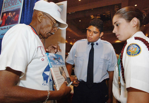 "Alexander Jefferson ,83,(left) a original Tuskegee Airmen, pilot , Class 44-A show his recently written book to Christian Roman, 16, West Orange High  Air Force ROTC (center), and Adriane Oliveira ,16,Cypress Creek High School ,Air Force ROTC at the 34th annual convention of Tuskegee Airmen. The Tuskegee Airmen were the first black Air Force unit to fight during World War II, and ultimately helped the integration of the U.S. military. Fewer than 4,000 of the 15,000 members of the so-called ""Tuskegee Experience"" remain, and many are gathering in Orlando this week for the 34th annual convention of Tuskegee Airmen Inc. Among the group's interests are outreach, particularly among children, and Wednesday's event will center on youth, with kids from local schools learning about NASA's space program and airplanes. They'll also have lunch with the Airmen."