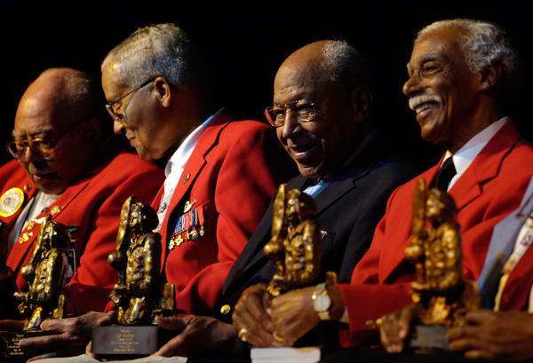 Retired Tuskegee Airmen (l-r) Lt. Col. Hiram Mann, Col. Charles McGee, Maj. Joe Gomer and Richard Rutledge hold their commemorative statues during a ceremony at the African American Research Library in Fort Lauderdale honoring the mens' service during WWII.  The Tuskegee Airmen were the first black pilots who served in WWII.