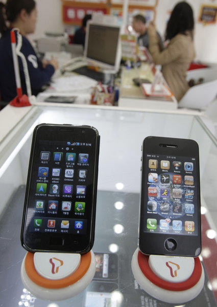 A federal judge denied Apple's request to increase its $1-billion patent infringement judgment against Samsung. Above, a Samsung Galaxy S smartphone, left, and Apple's iPhone 4 at a store in Seoul in 2011.
