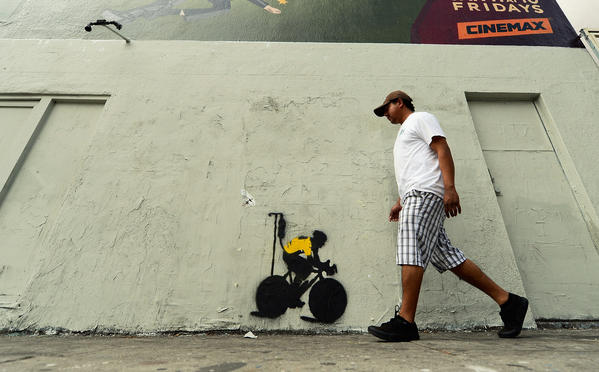A man walks past a stencil graffiti depicting cyclist Lance Armstrong in a yellow jersey, the traditional garb of the seven-time Tour De France winner, attached to an IV drip in Los Angeles, Calif.