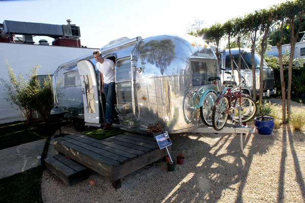 Architect Matthew Hofmann exits one of the vintage Airstream trailers he renovated.