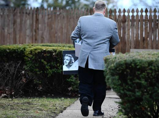 Homer Ryan, son of former Illinois Gov. George Ryan, carries a picture of his late mother Lura Lynn into his father's home in Kankakee, Ill. George Ryan was released from a halfway house to his home in Kankakee after serving a sentence in a federal prison for corruption.